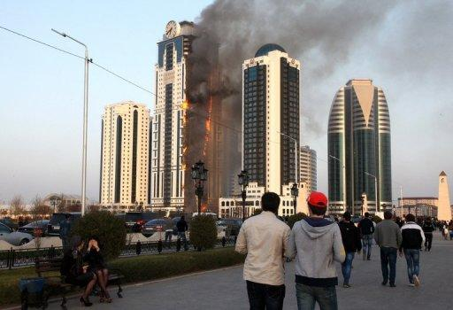 Chechen people look at burning skyscraper in central Grozny on April 3, 2013.