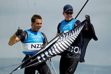 New Zealand's Peter Burling and Blair Tuke celebrate as they cross the finish line to win silver in the 49er sailing class at the London 2012 Olympic Games