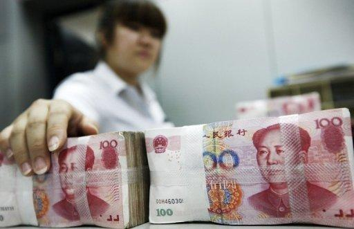 A clerk counting stacks of 100 yuan notes at a bank in Huaibei, east China's Anhui province