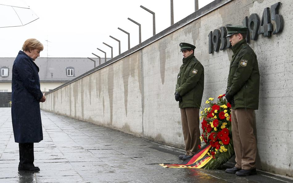 German Chancellor Merkel observes a moment of silence as she lays a wreath during a ceremony at the memorial in the former German Nazi concentration camp in Dachau