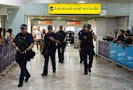 Armed police officers walk in front of the arrival gate at Heathrow airport, London, four days ahead of the London 2012 Olympic Games
