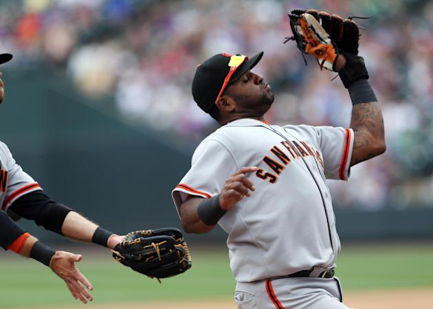 San Francisco Giants third baseman Pablo Sandoval snares a pop fly off the bat of Colorado Rockies' Troy Tulowtizki to end the fourth inning of a baseball game in Denver, Wednesday, April 23, 2014