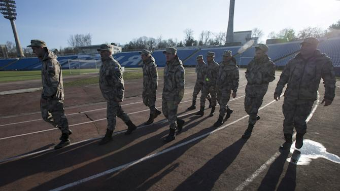 File photo of members of the People's Militia of Crimea walking near the pitch after a soccer match in Simferopol