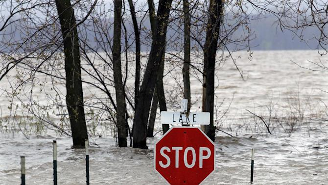 A stop sign is srrounded by water asthe Illinois River rises out of it's banks Tuesday, April 23, 2013, in Spring Bay Ill. Floodwaters are rising to record levels along the Illinois River in central Illinois. Communities in Illinois and Missouri are hoping to hold back surging rivers swollen by days of drenching rain. (AP Photo/Seth Perlman)