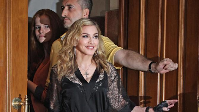 U.S. singer Madonna walks towards her fans at the opening of the new fitness club in Moscow, Russia, Monday, Aug. 6, 2012 (AP Photo/Mikhail Metzel)