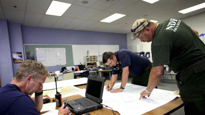 From left, Brad Washa, and J.W. McCoy, both with the Bureau of Land Management, and Tim Woolever, type 1 fire operations trainee with the Nevada Division of Forestry, work in the operations and resources room at Centennial High School, the Carpenter 1 fire command center, in Las Vegas, Monday, July 8, 2013. The wildfire, which encompasses thousands of acres, began last Monday. (AP Photo/Las Vegas Review-Journal, Jessica Ebelhar) LOCAL TV OUT; LOCAL INTERNET OUT; LAS VEGAS SUN OUT