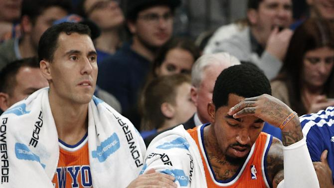 New York Knicks' Pablo Prigioni, left, pats the arm of teammate J.R. Smith, right, late in the second half of an NBA basketball game against the Atlanta Hawks Saturday, Nov. 16, 2013, in New York.  Atlanta defeated New York 110-90