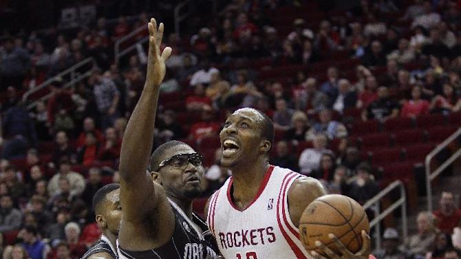 Houston Rockets power forward Dwight Howard (12) is fouled by Orlando Magic's Jason Maxiell (54) as he attempts to drive during the second half of an NBA basketball game on Sunday, Dec. 8, 2013, in Houston
