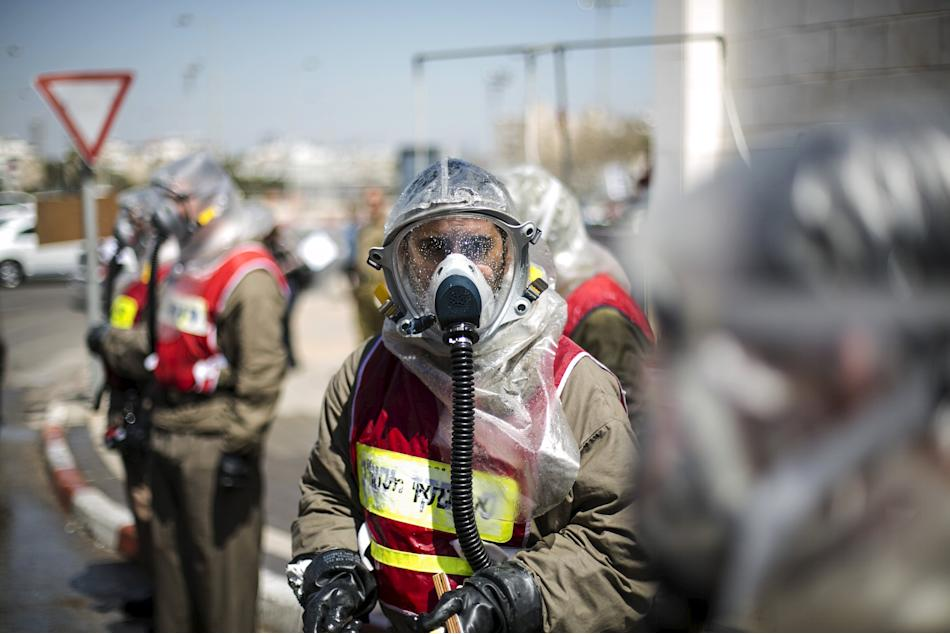 An Israeli Defence Force reservist from the Home Front Command wears a protective suit during an exercise, together with hospital staff, simulating a chemical warfare attack at a hospital near Tel Avi