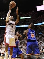 Forward LeBron James (L) of the Miami Heat shoots over J.R. Smith of the New York Knicks in Game One of the Eastern Conference quarter-finals in the 2012 NBA Playoffs at the American Airines Arena in Miami, Florida. Miami routed the New York Knicks 100-67