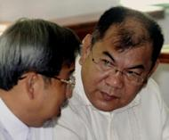 Former military finance official Major General Carlos Garcia (right) talks to his lawyer in a hearing room at a military court in Manila on December 2, 2005. The Philippine Supreme Court on Wednesday blocked efforts by a senior general facing massive graft charges to enter a plea bargain which would have let him post bail and walk free in a few years, keeping much of the money