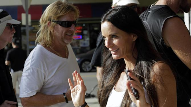 """In this July 24, 2013, photo, actress Gabrielle Anwar takes a break during taping for an episode of """"Burn Notice"""" in Miami. The cable spy drama is coming to an end after seven seasons with a big finale next Thursday, Sept. 12, 2013. (AP Photo/Alan Diaz)"""