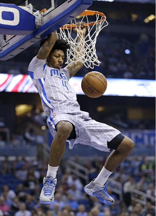 Orlando Magic's Elfrid Payton (4) hangs on the rim after making an uncontested dunk against the San Antonio Spurs during the first half of an NBA basketball game, Wednesday, April 1, 2015, in Orla