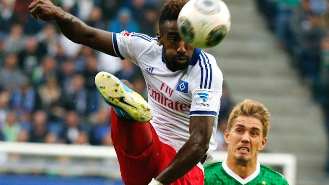 Bremen's Nils Petersen, right,  right, challenges  for the ball with Hamburg's Johan Djourou during the German Bundesliga soccer match between Hamburger SV and SV Werder Bremen  in Hamburg, Germany, Saturday Sept. 21, 2013