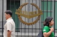 Pedestrians walk past a logo of the Asian Development Bank (ADB) displayed outside its headquarters in Manila, 2010. Asian Development Bank said that free trade agreements cannot be credited for the increase in intra-Asian trade as they are often restrictive in scope and difficult to implement