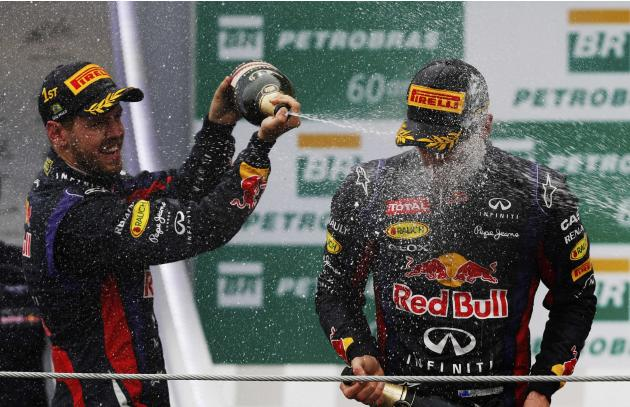 Mark Webber of Australia is sprayed with champagne by Sebastian Vettel of Germany and Fernando Alonso of Spain during podium celebrations after the Brazilian F1 Grand Prix at the Interlagos circuit in