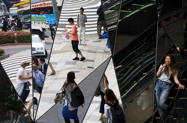 File photo of people reflected in mirrors at an entrance to a department store in the fashion district of Harajuku