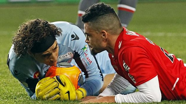 AS Monaco's Emmanuel Riviere (R) looks at Ajaccio's goalkeeper Memo after falling during their French Ligue 1 match at Louis II stadium December 8, 2013 (Reuters)