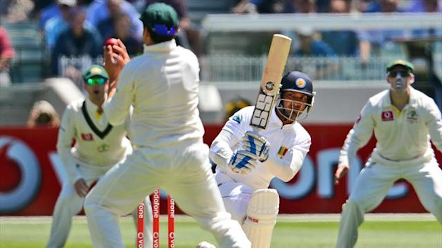 Sri Lankan batsman Kumar Sangakkara (2nd R) drives a ball at Australian fieldsman Ed Cowan (2nd L) on the first day of the second cricket Test