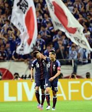 Japan's forward Shinji Kagawa (L) is congratulated by his captain Makoto Hasebe (R) during their 2014 World Cup Asian qualifier football match against Jordan in Saitama