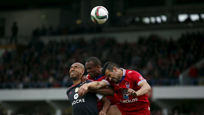 Benfica's Luisao fights for the ball with Gil Vicente's Ricardo Cadu and Evaldo dos Santos during their Portuguese premier league soccer match at Cidade de Barcelos stadium in Barcelos