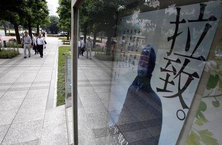 People walk near a campaign poster on Japan's abduction issue on a street in Tokyo July 3, 2014. REUTERS/Yuya Shino/Files