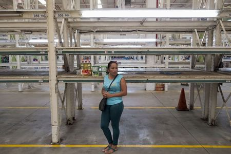 A woman stands next to empty shelves inside a Makro supermarket in Caracas. (Reuters)