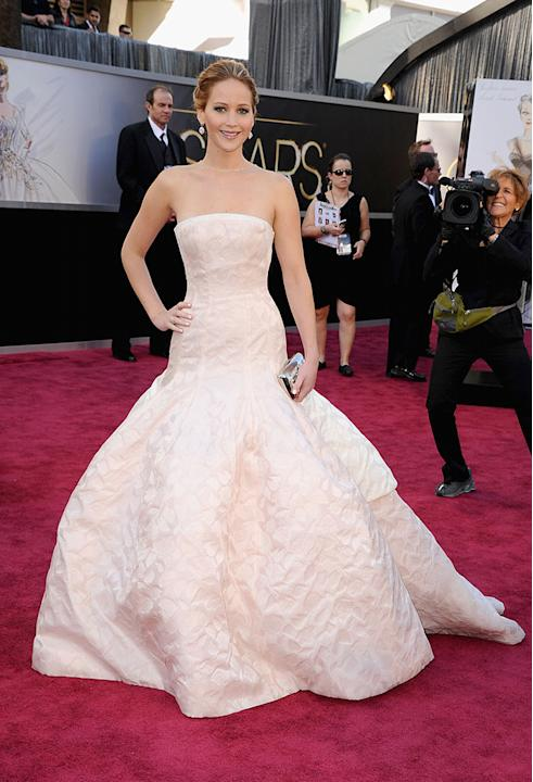 """Best Actress front-runner Jennifer Lawrence (""""Silver Linings Playbook"""") hit the red carpet at the 2013 Oscars in a confusing dress. Is she trying to be a bride? The all-white strapless numbe"""