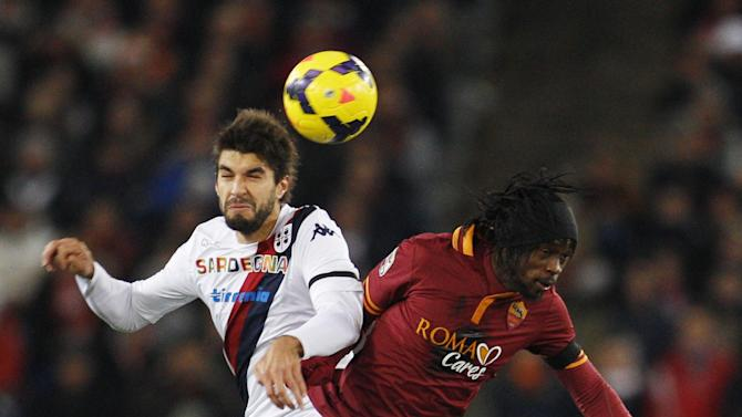 Cagliari defender Luca Rossettini, left, and AS Roma forward Gervinho, of Ivory Coast, jump for the ball during a Serie A soccer match between As Roma and Cagliari, at Rome's Olympic stadium, Monday, Nov. 25, 2013