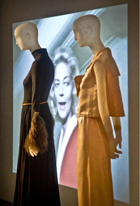 This March 3, 2015 photo shows a video projection of the late actress Lauren Bacall flanked by mannequins wearing her designer garments, Christian Dior, left, and Norman Norell during a preview of the