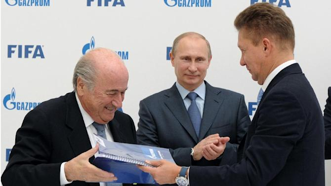 Russian President Vladimir Putin, center, applauds as FIFA President Sepp Blatter, left, and  Russian gas monopoly Gazprom Head Alexei Miller exchange documents after signing a partnership agreement between FIFA and Gazprom in the Black Sea resort of Sochi, Russia, Saturday, Sept. 14, 2013