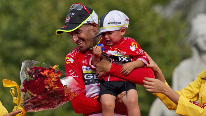 Geox-TMC team member Juan Cobo and his nephew Hugo, celebrates his victory on the podium in the Spanish Vuelta in Madrid, Spain, Sunday, Sept. 11, 2011. (AP Photo/Arturo Rodriguez)