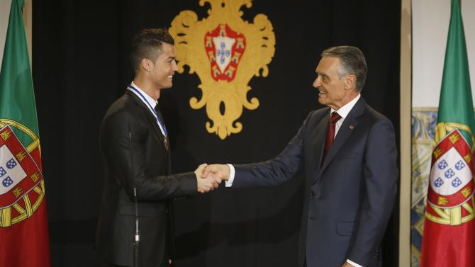 Portugal's soccer team captain Ronaldo shakes hands with Portugal's President Silva after he was decorated with the Ordem do Infante Dom Henrique in Lisbon