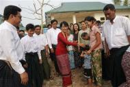 Aung San Suu Kyi is greeted outside a polling station during a visit in Kawhmu township