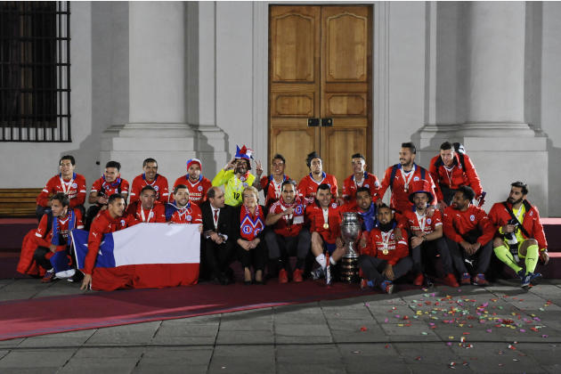 Chile's President Michelle Bachelet, center, poses with Chile's soccer players after they won the Copa America trophy at the presidential palace in Santiago, Chile, late Saturday, July 4, 2015