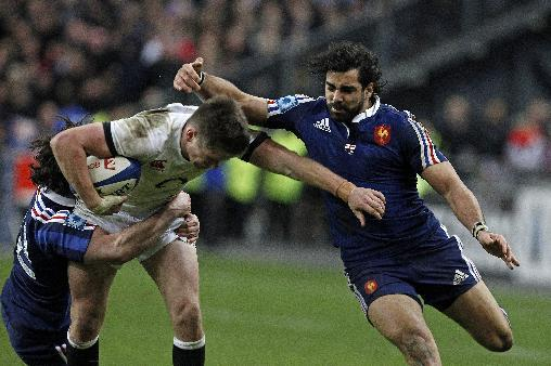 England's Owen Farrell is tackled by France's Yoann Huget, right, and Maxime Machenaud, during their Six Nations rugby union international match, at the Stade de France, in Saint Denis, outside Paris, Saturday, Feb 1, 2014. France defeated England 26-24