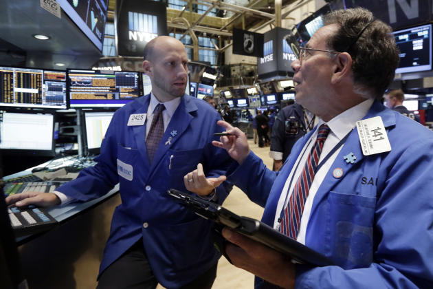 Specialist Meric Greenbaum, left, and trader Sal Suarino work on the floor of the New York Stock Exchange, Friday, Oct. 2, 2015. A weak report on the U.S. jobs market is sending the stock market and t