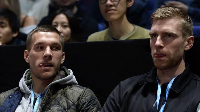 Arsenal soccer players Podolski of Germany and fellow compatriot Mertesacker watch Berdych of Czech Republic take on Nadal of Spain in their men's singles tennis match in London