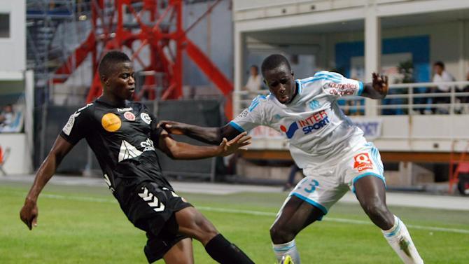 Stade de Reims' midfielder Prince Oniangue, left, challenges for the ball with Marseille's defender Benjamin Mendy during their League One soccer match, at the Velodrome Stadium, in Marseille, southern France, Saturday, Oct. 26, 2013