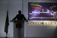 Former Prime Minister Ali Benflis is silhouetted against a banner featuring his name and word 'president' during a news conference to announce his candidacy for the presidential election in Algiers January 19, 2014. REUTERS/Louafi Larbi