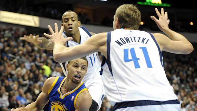 Golden State Warriors point guard Stephen Curry (30) drives between Dallas Mavericks shooting guard Monta Ellis (11) and power forward Dirk Nowitzki (41) in the first half during an NBA basketball game on Wednesday, Nov. 27, 2013, in Dallas