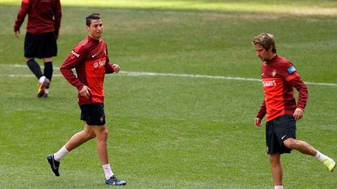 Portugal's Cristiano Ronaldo and Fabio Coentrao, right, play with a ball during a training session Sunday, Nov. 17 2013, at the Luz stadium in Lisbon. Portugal will play Sweden Tuesday in a World Cup qualifying playoff second-leg soccer match