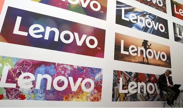 A man uses his laptop next to Lenovo's logos during the Mobile World Congress in Barcelona