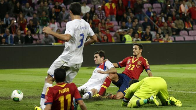 Spain's Jesus Navas, right, scores his side's second goal past Chile's Eugenio Mena, third right, and goalkeeper Claudio Bravo, right, as Spain's Pedro Rodriguez (11), and Chile's Marcos Gonzalez (3) look on during a friendly soccer match between Spain and Chile at the Stade de Geneve stadium, in Geneva, Switzerland, Tuesday, Sept. 10, 2013