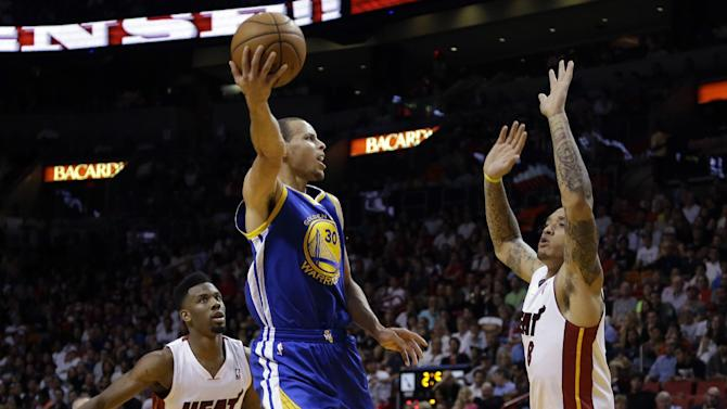 Golden State Warriors' Stephen Curry (30) shoots between Miami Heat's Norris Cole (30) and Michael Beasley (8) during the second half of an NBA basketball game, Thursday, Jan. 2, 2014, in Miami. The Warriors defeated the Heat 123-114