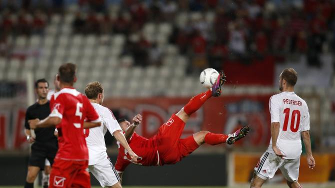 Malta's Camilleri attempts an overhead kick as Denmark's Eriksen and Pedersen look on during their 2014 World Cup qualifying soccer match at the National Stadium in Ta' Qali, outside Valletta