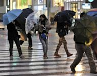 This file photo shows pedestrians crossing a street on a rainy in Tokyo, earlier this month. Japan's unemployment rate was unchanged at 4.5 percent in March, the internal affairs ministry said on Friday, in line with economists' expectations