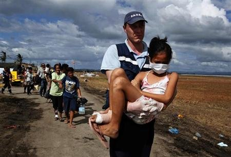 A volunteer from a French rescue team carries an injured girl to a military plane during an evacuation at Tacloban airport in the Typhoon Haiyan devastated city of Tacloban November 16, 2013. REUTERS/Bobby Yip