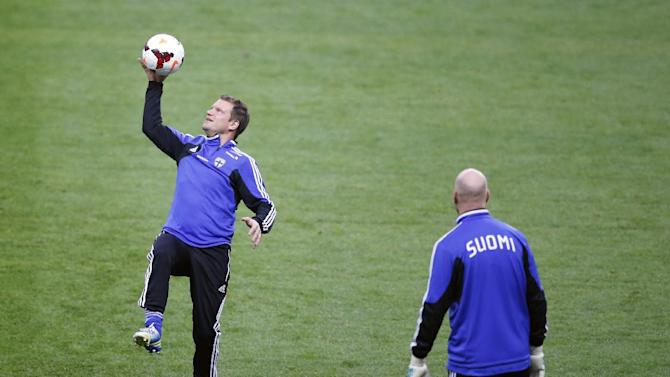 Finland's soccer captain Teemu Tainio, left controls the ball during a training session at the Stade de France stadium in Saint Denis, north of Paris, Monday, Oct. 14, 2013, ahead of their 2014 World Cup Group I qualifying soccer match against France