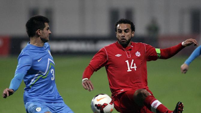 Slovenia's Gregor Balazic, left, is challenged by Canada's Canada's Dwayne De Rosario during a friendly soccer match between Slovenia and Canada, in Celje, Slovenia, Tuesday, Nov. 19, 2013
